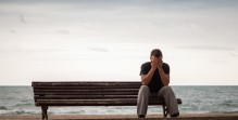 Sad man sits on an old wooden bench on the sea coast