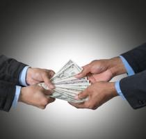 Businessman recieving the money offered by businessman on dark b