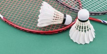 Two new badminton shuttlecock with rackets on green mat court