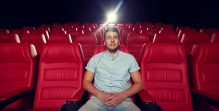 happy young man watching movie in theater