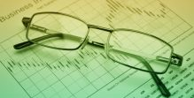 Glasses on stock market graph, financial concept