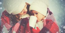 happy family mother and child drinking hot tea on winter walk outdoors
