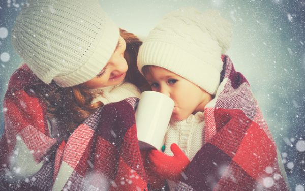 happy family mother and child daughter drinking hot tea on a winter walk outdoors