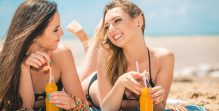 Beautiful young girls drinking water from boutle on the beach