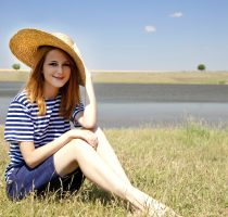 Beautiful redhead girl at countryside nead lake.
