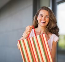 Portrait of smiling young woman showing shopping bag
