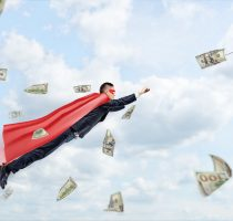 A businessman wearing a red superhero cape flying through the clouds following a dollar bill.