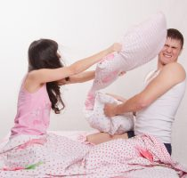 Young couple in bed arranged a pillow fight