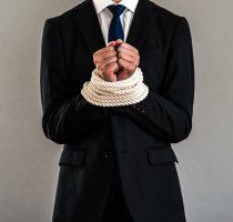 ロープで手を縛られたビジネスマン