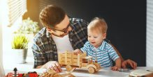 father and son toddler gather craft a car out of wood and play