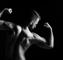 The back view torso of attractive male body builder on black background.
