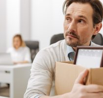 Frightened fired employee holding the box in the office